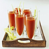 Several glasses of tomato juice on a tray