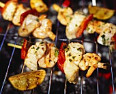 Several seafood kebabs on a barbecue