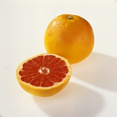 One whole and one half pink grapefruit