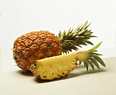 A whole pineapple and a wedge of pineapple