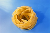 Tagliatelle rolled up on blue background