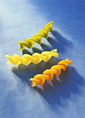 Three coloured fusilli on blue background