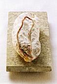 A whole Italian salami on a stone slab