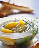Cold avocado soup with orange wedges