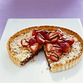 Chocolate and walnut tart with strawberries, a piece cut