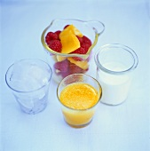 Four glasses filled with mango, raspberries, ice cubes and milk