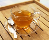 Glass cup of black tea on a wooden tray
