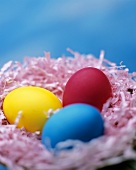 Three coloured Easter eggs in an Easter nest