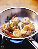 Frying shrimps with herbs in a frying pan