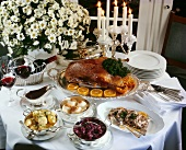 Laid table with roast goose, accompaniments and red wine