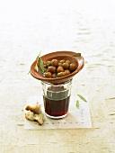 Ein Schälchen mit grünen Oliven auf einem Glas Wein