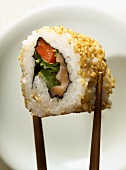 Inside-out roll with fish between chopsticks
