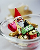 A glass bowl with a chocolate Father Christmas & other sweets