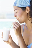 Young woman drinking milkshake on beach