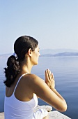 Young woman meditating on a jetty by water