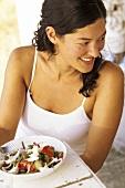 Junge Frau sitzt vor einem Teller griechischen Salat