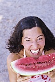 Young woman holding a wedge of watermelon with a bite taken