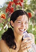 Young woman drinking mineral water in the shade