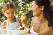 Mother and daughter eating salad in open air
