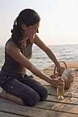 Junge Frau öffnet Weissweinflasche auf einem Steg