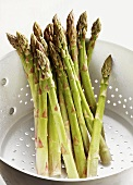 Several spears of green asparagus in a metal colander