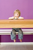 Small boy drinking milk at wooden table