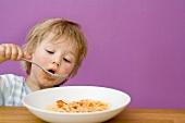 Small boy eating spaghetti with tomato sauce