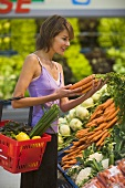 Young woman at the vegetable counter in a supermarket