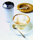Cappuccino, Zuckerspender und Zigarette im Aschenbecher
