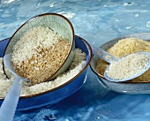 Various types of rice in bowls, floating in water
