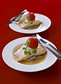 Poached salmon trout on noodles in tomato broth