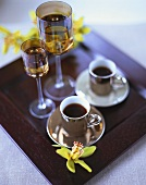 Two cups of black coffee and liqueur on tray