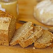 Wholemeal bread, slices cut, jar of honey behind