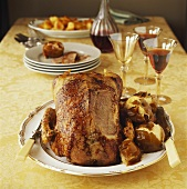 Roast goose with potatoes and red wine on laid table