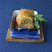 Stuffed rolled pork joint in roasting dish
