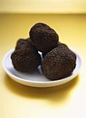 Black truffles on white plate
