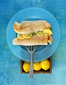 Fresh cod fillets with lemons on blue plate