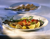 Trout wrapped in bacon with herbs and lemons
