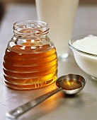 Honey in jar and on spoon; yoghurt; milk