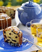 Piece of blueberry cake with glacé icing; tea glasses; teapot
