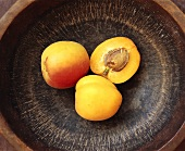 Two whole apricots and half an apricot on brown plate