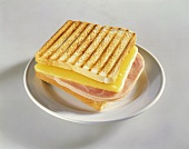 Ham and cheese on toast on white plate