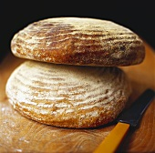 Two loaves of bread on wooden background