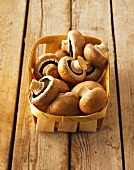 Brown mushrooms in chip basket on wooden background