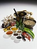 Various spices, arranged around a mortar