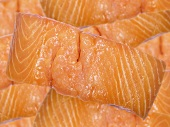 A salmon fillet with lots of salmon fillets in background
