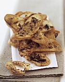 Crisp olive bread in slices on napkin
