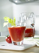 Tomato juice in glass with ice cubes and celery