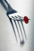 Red vitamin capsule on fork