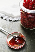 Redcurrants in jar, redcurrant jelly on spoon